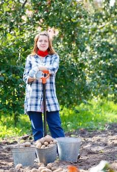 Menina com uma pá e um balde de batatas ao ar livre