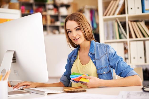 Menina com uma paleta de cores e um computador