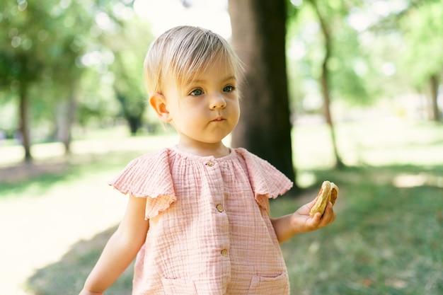 Menina com uma panqueca na mão em um gramado verde