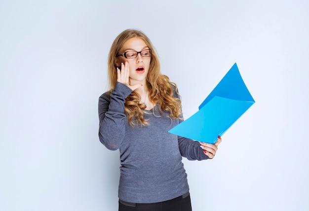 Menina com uma pasta azul levantando a mão para chamar a atenção.