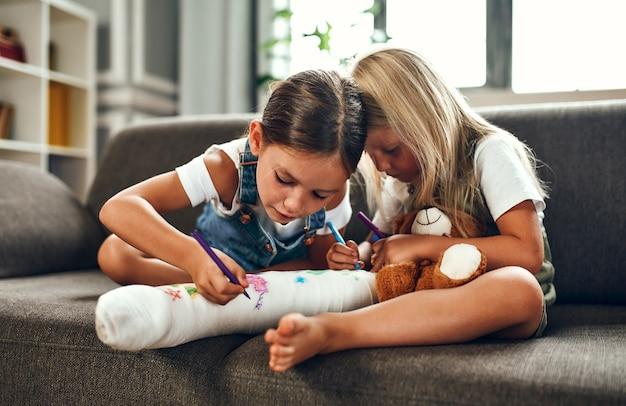 Menina com uma perna quebrada no sofá. duas irmãs desenham com canetas hidrográficas em uma bandagem de gesso. as crianças se divertem e brincam no sofá da sala.