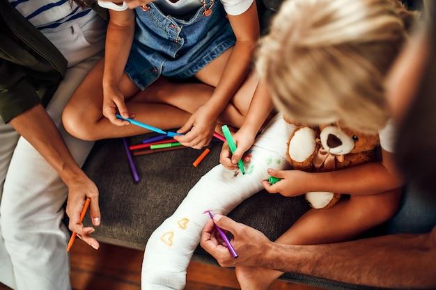 Menina com uma perna quebrada no sofá. mamãe, papai e duas filhas desenham em gesso com canetas hidrográficas. a família toda se diverte em casa.