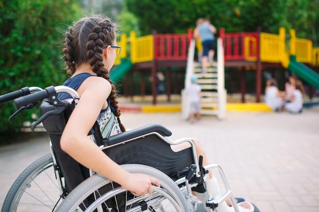 Menina com uma perna quebrada senta-se em uma cadeira de rodas em frente ao parque infantil