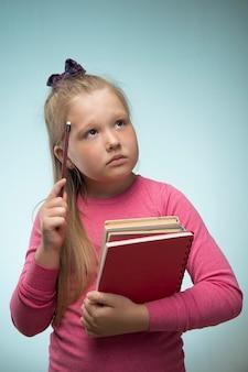 Menina com uma pilha de livros e um lápis nas mãos em uma parede azul. volta às aulas e conceito de educação
