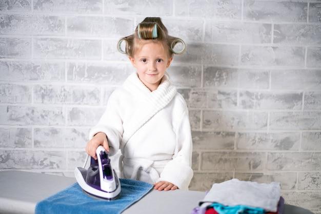 Menina com uma quantidade de roupa a ser passada a ferro, com um jaleco branco com rolinhos na cabeça