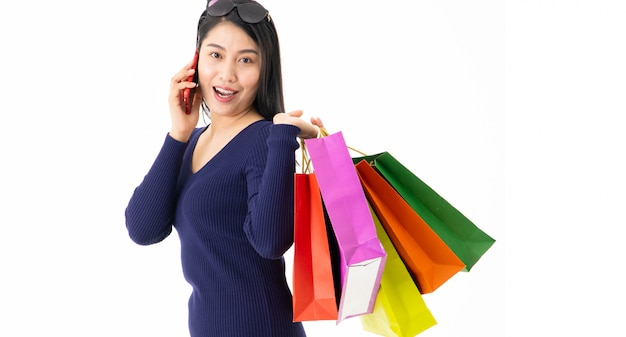 Menina com uma sacola de compras andando no celular, falando em branco feliz com as compras
