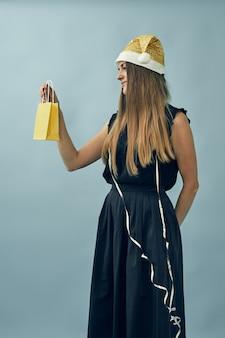 Menina com uma sacola de presente nas mãos e um chapéu de papai noel