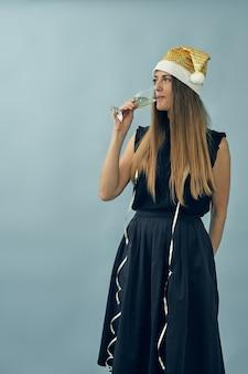 Menina com uma taça de champanhe e um chapéu de papai noel