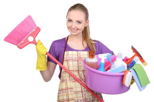 Menina com uma vassoura e aparelhos para limpeza do quarto.