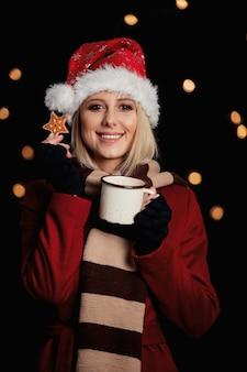 Menina com uma xícara de café e biscoito de gengibre