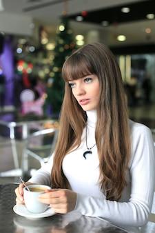 Menina com uma xícara de café em um shopping no fundo da árvore de natal