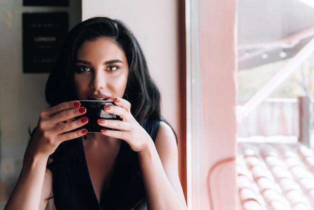 Menina com uma xícara de cappuccino em um café
