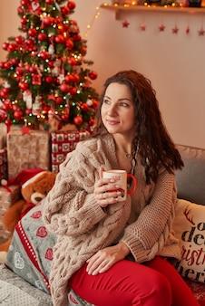 Menina com uma xícara de marshmallow no interior do ano novo em casa