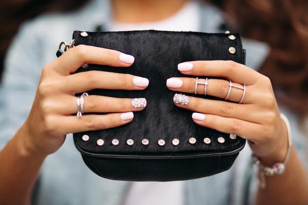 Menina com unhas feitas com belo ornamento em alianças, segurando o saco de pele preta.