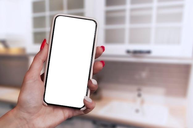 Menina com unhas lindas detém um close-up de maquete de smartphone isolado em um fundo de cozinha.