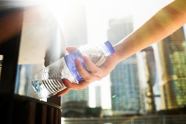 Menina com unhas vermelhas coloca uma garrafa de água com scrapheap