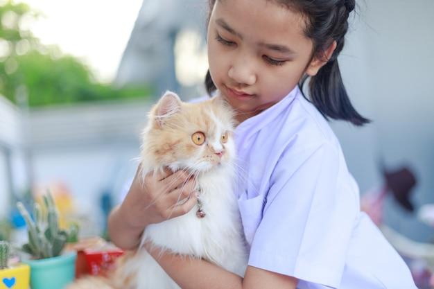Menina com uniforme de estudante tailandês abraçando seu gato persa
