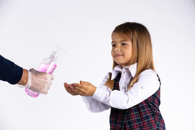 Menina com uniforme escolar desinfetando as mãos com gel desinfetante à base de álcool durante o vírus corona