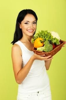 Menina com vegetais na superfície verde