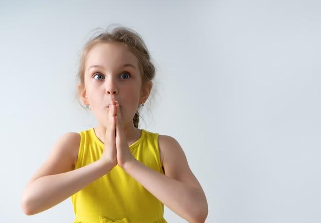 Menina com vestido amarelo parecendo preocupada ou com medo, com os olhos bem abertos e as mãos cruzadas