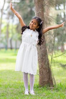 Menina com vestido branco muito feliz e sorridente na floresta