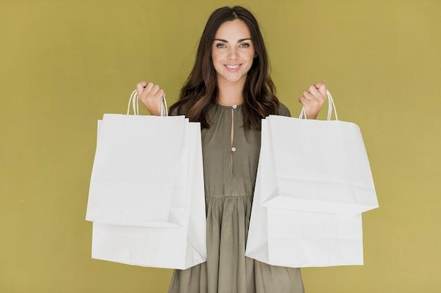 Menina com vestido cáqui, pegar redes de compras