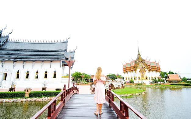 Menina com vestido cruzando uma ponte em frente ao salão do trono dusit maha prasat na tailândia