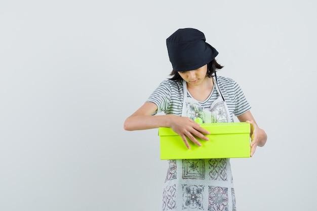 Menina com vestido de cozinha olhando para a caixa de presente e parecendo curiosa,