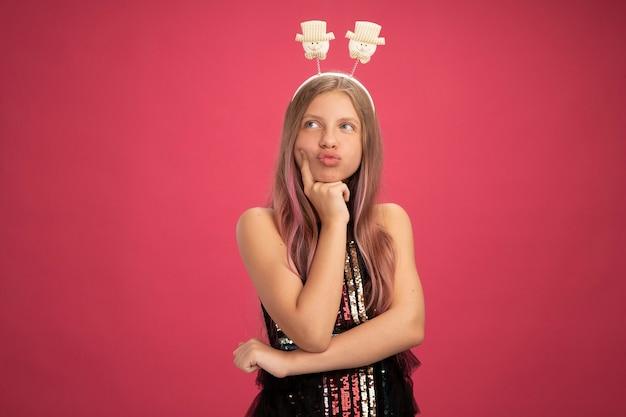 Menina com vestido de festa brilhante e bandana engraçada olhando de lado confusa, conceito de feriado de celebração de ano novo em pé sobre fundo rosa