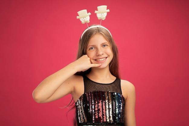 Menina com vestido de festa brilhante e bandana engraçada olhando para a câmera, sorrindo, fazendo gesto de me ligar, conceito de feriado de celebração de ano novo em pé sobre fundo rosa