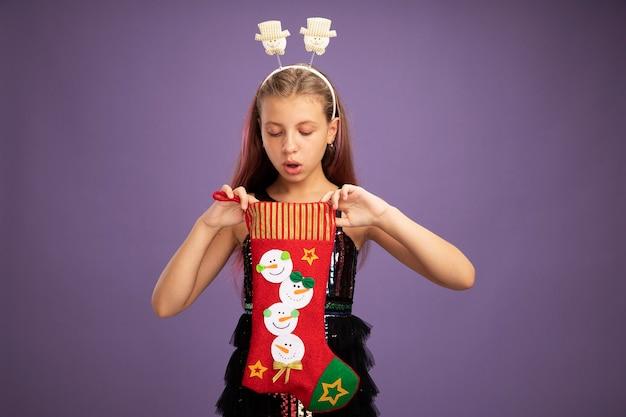 Menina com vestido de festa brilhante e bandana engraçada segurando uma meia de natal, olhando para dentro, intrigada em pé sobre um fundo roxo