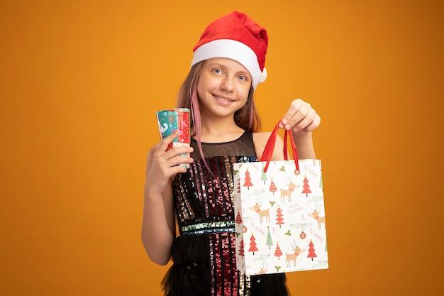 Menina com vestido de festa brilhante e chapéu de papai noel segurando dois copos de papel coloridos e um saco de papel com presentes olhando para a câmera sorrindo alegremente em pé sobre um fundo laranja