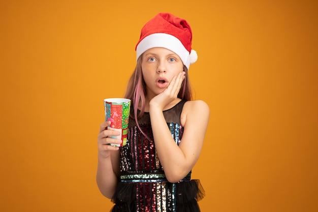 Menina com vestido de festa brilhante e chapéu de papai noel segurando dois copos de papel coloridos, olhando para a câmera espantada e surpresa em pé sobre um fundo laranja