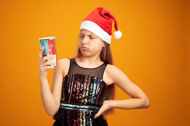 Menina com vestido de festa brilhante e chapéu de papai noel segurando dois copos de papel coloridos olhando para ele confusa em pé sobre a parede laranja