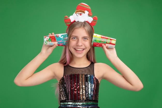 Menina com vestido de festa brilhante e tiara de papai noel segurando copos de papel coloridos sobre as orelhas, sorrindo alegremente em pé sobre a parede verde