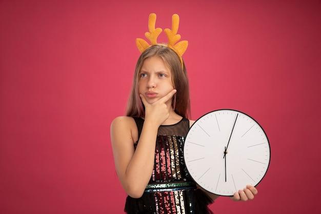 Menina com vestido de festa brilhante e tiara engraçada com chifres de veado segurando um relógio olhando de lado confusa, conceito de feriado de celebração de ano novo em pé sobre fundo rosa