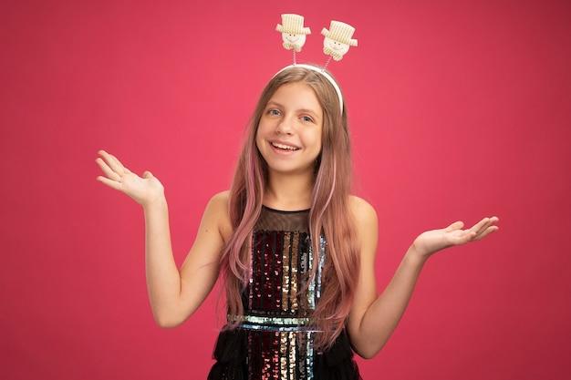 Menina com vestido de festa brilhante olhando para a câmera com uma cara feliz sorrindo alegremente conceito de feriado de celebração de ano novo em pé sobre fundo rosa