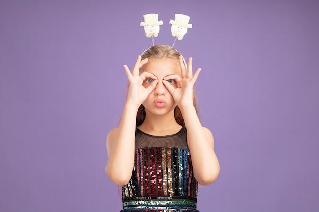 Menina com vestido de festa glitter e bandana engraçada olhando para a câmera com os dedos, fazendo gesto binocular em pé sobre fundo roxo