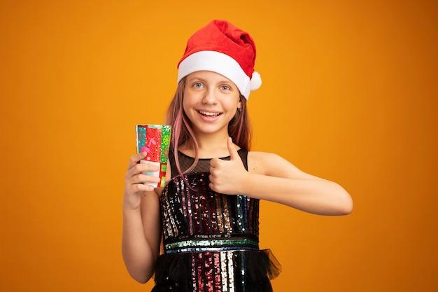 Menina com vestido de festa glitter e chapéu de papai noel segurando dois copos de papel coloridos, olhando para a câmera, sorrindo e mostrando os polegares em pé sobre um fundo laranja