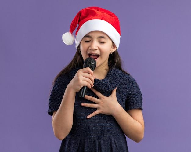 Menina com vestido de malha com chapéu de papai noel segurando o microfone e cantando para celebrar a festa de natal feliz e positiva em pé sobre a parede roxa