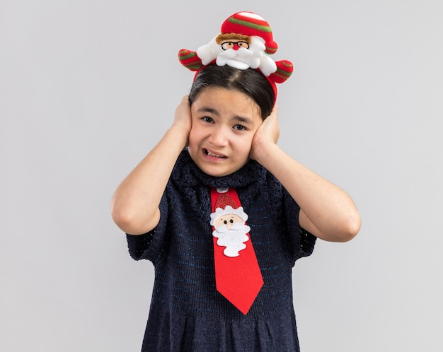 Menina com vestido de malha com gravata vermelha e aro de natal engraçado na cabeça cobrindo as orelhas com as mãos com expressão irritada