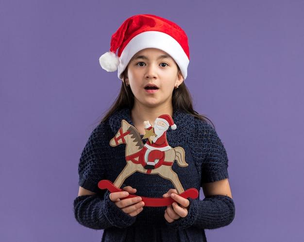 Menina com vestido de malha e chapéu de papai noel segurando um brinquedo de natal parecendo surpresa