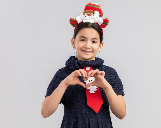 Menina com vestido de malha usando gravata vermelha com aro de natal engraçado na cabeça olhando sorrindo fazendo um gesto de coração com os dedos