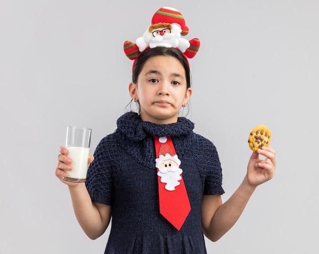 Menina com vestido de malha usando gravata vermelha com aro de natal engraçado na cabeça segurando um copo de leite e biscoito com expressão triste