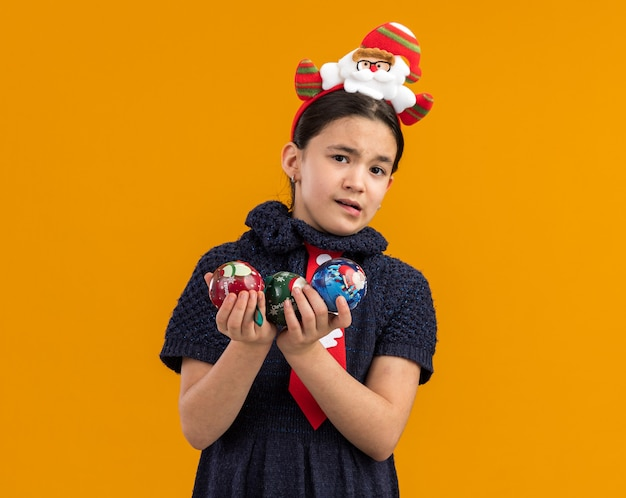 Menina com vestido de malha usando gravata vermelha com aro engraçado na cabeça segurando bolas de natal parecendo preocupada