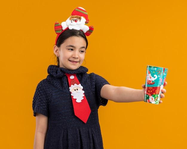 Menina com vestido de malha usando gravata vermelha com aro engraçado na cabeça segurando copo de papel colorido feliz e sorridente