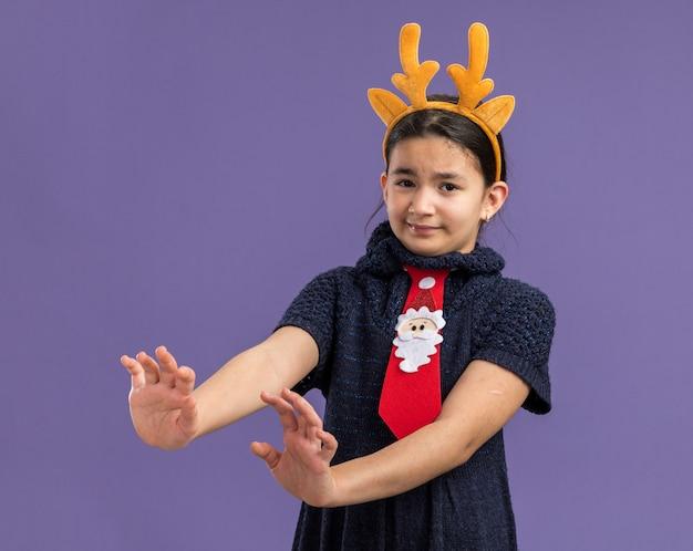 Menina com vestido de malha usando gravata vermelha com borda engraçada com chifres de veado na cabeça parecendo assustada fazendo gesto de defesa com as mãos em pé sobre a parede roxa