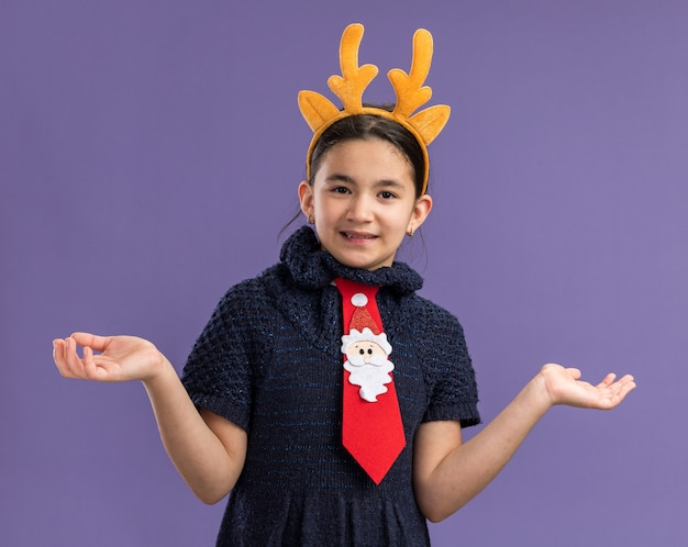 Menina com vestido de malha usando gravata vermelha com borda engraçada com chifres de veado na cabeça sorrindo confusa abrindo os braços para os lados em pé sobre a parede roxa