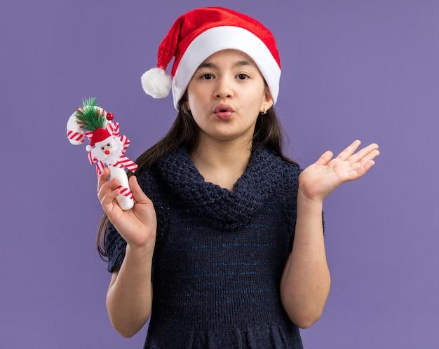 Menina com vestido de tricô com chapéu de papai noel segurando uma bengala de doces de natal surpresa com os braços levantados em pé sobre a parede roxa