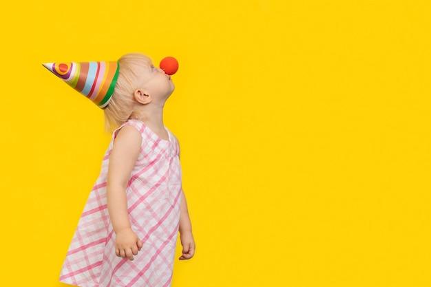Menina com vestido de verão, nariz de palhaço e chapéu de festa